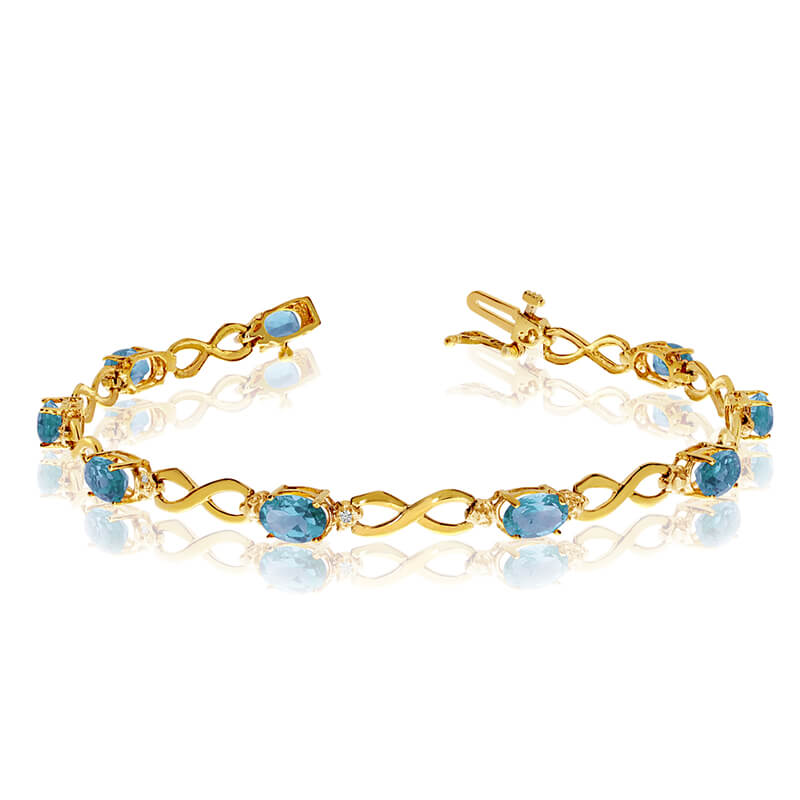 This 10k yellow gold oval blue topaz and diamond bracelet features nine 6x4 mm stunning natural b...