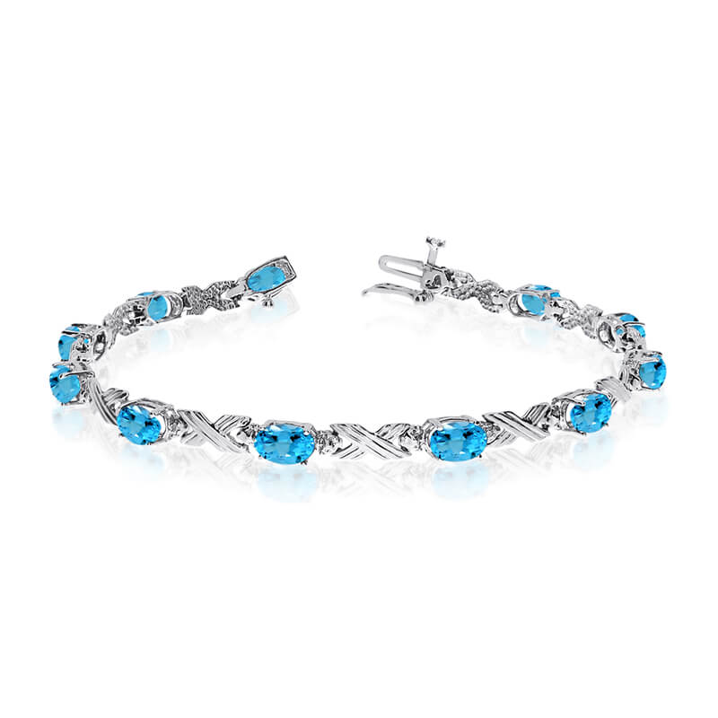 This 14k white gold oval blue topaz and diamond bracelet features eleven 6x4 mm stunning natural ...