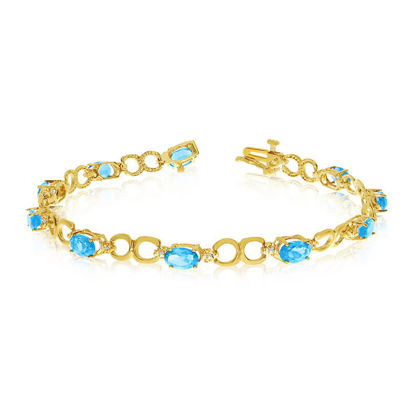 This 10k yellow gold oval blue topaz and diamond bracelet features ten 6x4 mm stunning natural bl...