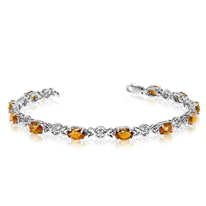 This 10k white gold oval citrine and diamond bracelet features eleven 6x4 mm stunning natural cit...