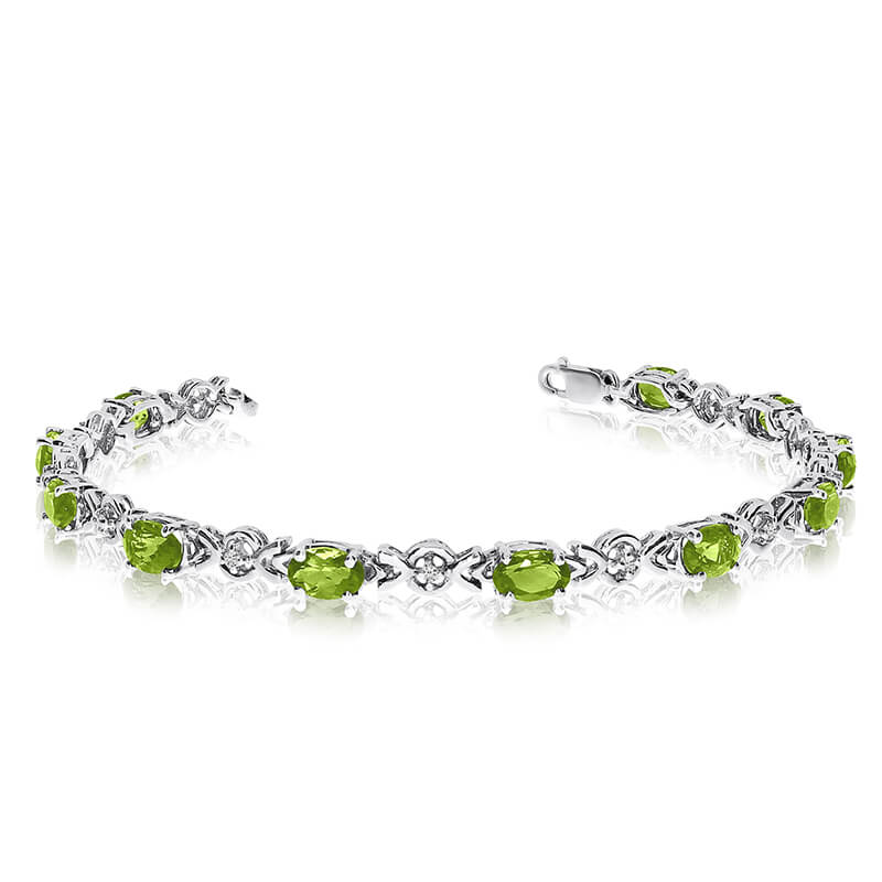This 14k white gold oval peridot and diamond bracelet features eleven 6x4 mm stunning natural per...