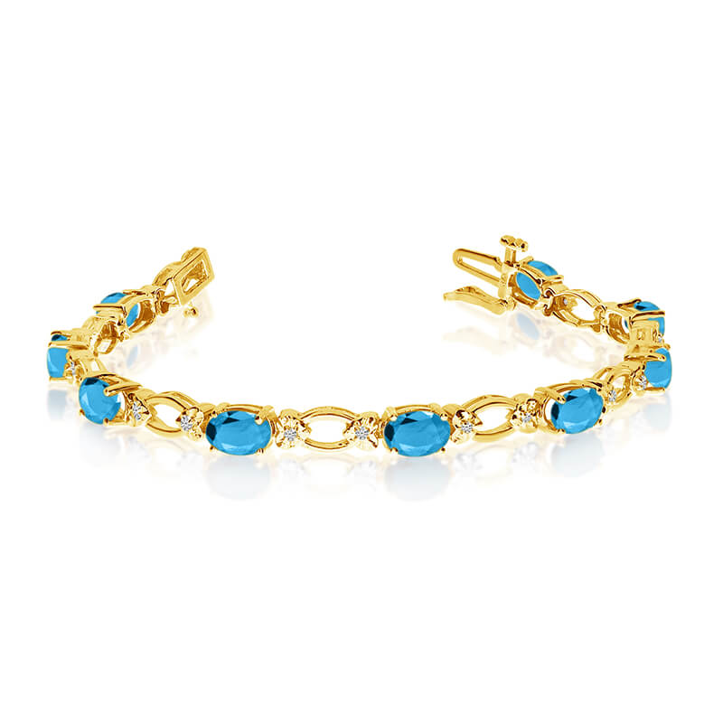 This 14k yellow gold natural blue-topaz and diamond tennis bracelet features 12 oval blue-topazs ...