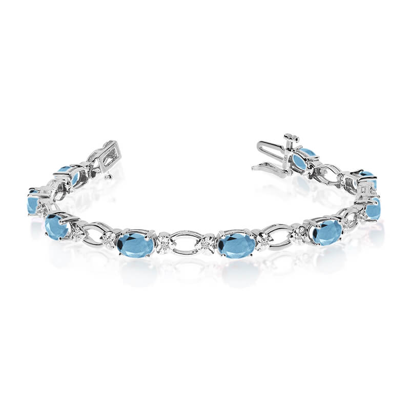 This 14k white gold natural aquamarine and diamond tennis bracelet features 12 oval aquamarines w...
