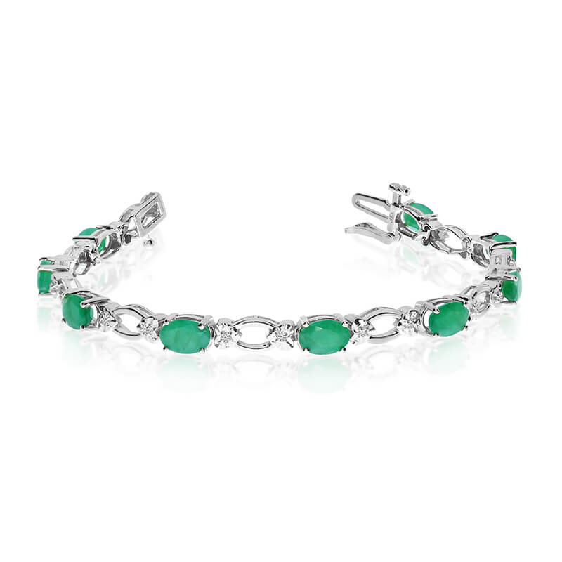 This 14k white gold natural emerald and diamond tennis bracelet features 12 oval emeralds with a ...