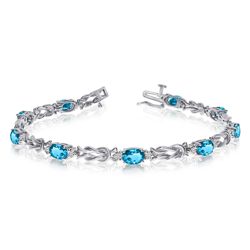 This 14k white gold natural blue-topaz and diamond tennis bracelet features 9 oval blue-topazs wi...