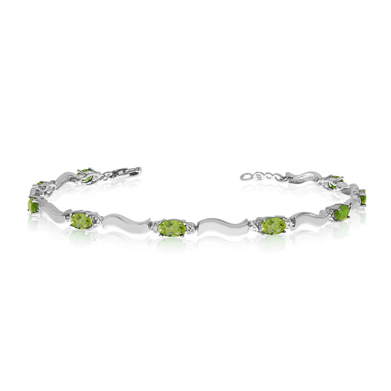 This 10K White Gold oval peridot and diamond bracelet features nine 5x3 mm stunning natural perid...