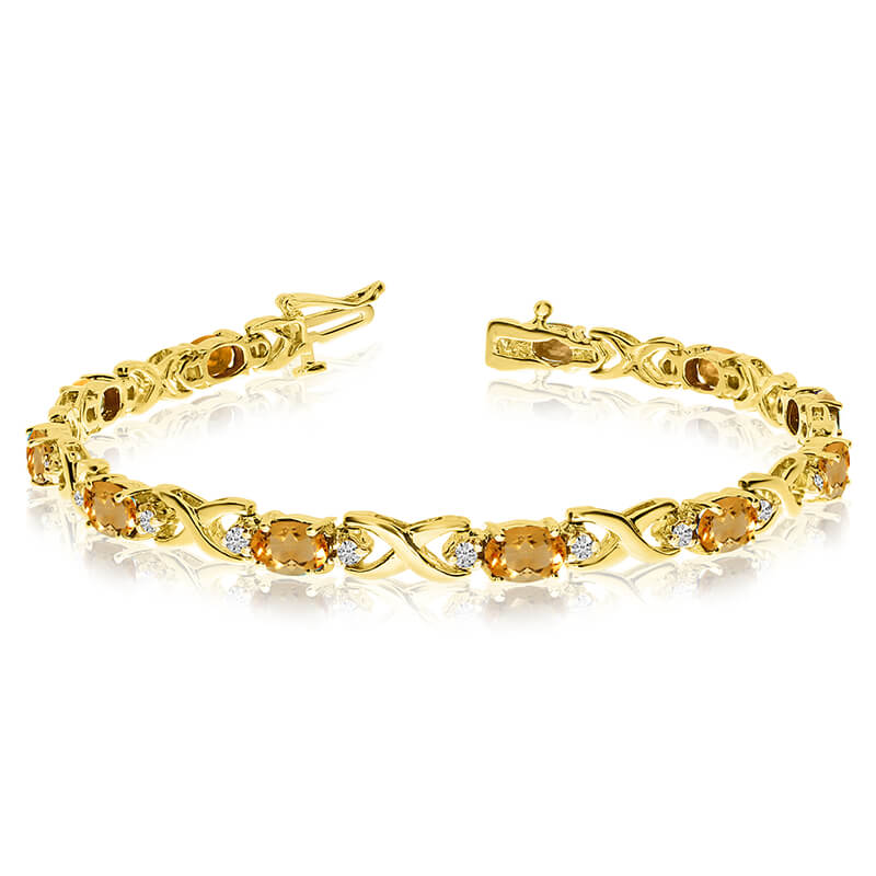 This 14k yellow gold natural citrine and diamond tennis bracelet features 11 oval citrines with a...