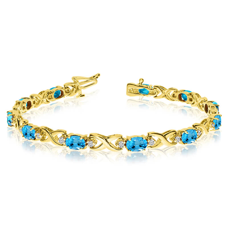 This 14k yellow gold natural blue-topaz and diamond tennis bracelet features 11 oval blue-topazs ...