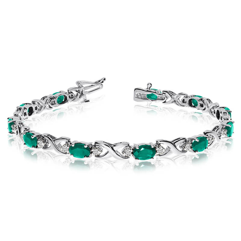 This 14k white gold natural emerald and diamond tennis bracelet features 11 oval emeralds with a ...
