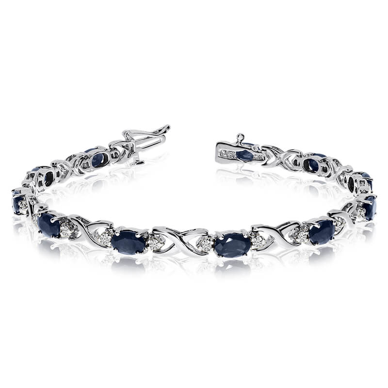 This 14k white gold natural sapphire and diamond tennis bracelet features 11 oval sapphires with ...