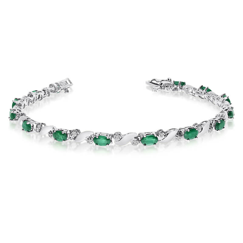 This 14k white gold natural emerald and diamond tennis bracelet features 13 oval emeralds with a ...