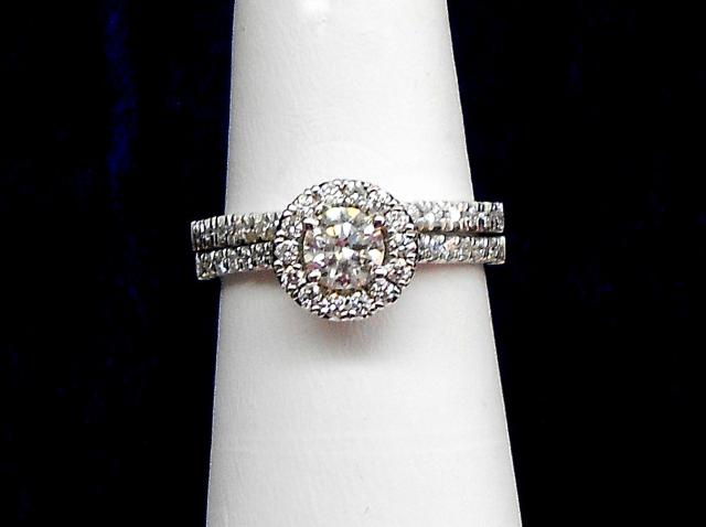 JCSJCS962: Engagement ring has 1/2 ct round center stone surrounded by .28 tcw of additional diamonds. Wedding band has .18 ctw of diamonds. Set totals .96 tcw set into 14kt white gold.