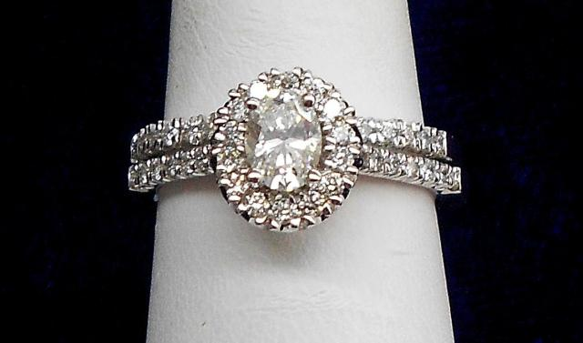JCSJCS963: Engagement ring features .50ct oval cut center stone surrounded by.33tcw of additional daiamonds. Wedding band has .17tcw of diamonds. Set totals at 1tcw. In 14kt white gold.