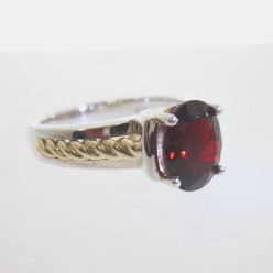 JCSJCS1386: The pictured ring is sterling silver accented in 18kt yellow gold. It is set with a 9 x 7mm red Garnet. There several mentions of garnet in the Bible!  SOLD