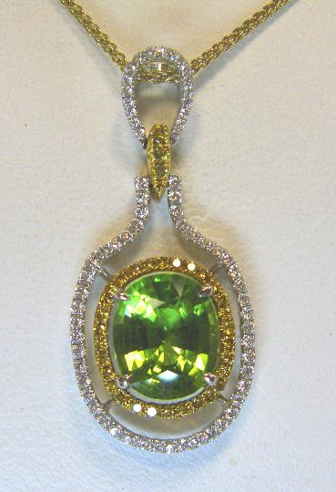 JCSA902: Gorgeous 18kt two tone, peridot and diamond pendant.  The pendant contains one oval 3.31ct. peridot (approx. 10.3 X 8.6mm's) set in the center.  The pendant also has .40cts. of round white diamonds and .25cts. of fancy yellow diamonds (16