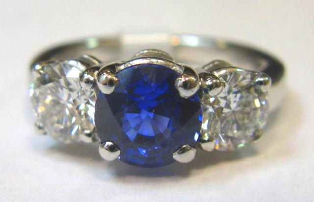 JCSA910: Sapphire and diamond estate ring.  Round sapphire is 1.30cts. and diamonds total 1.30cts.  The mounting is platinum.